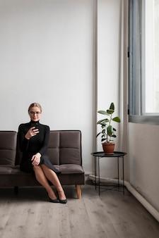 Vrouw op bank mobiel gebruiken