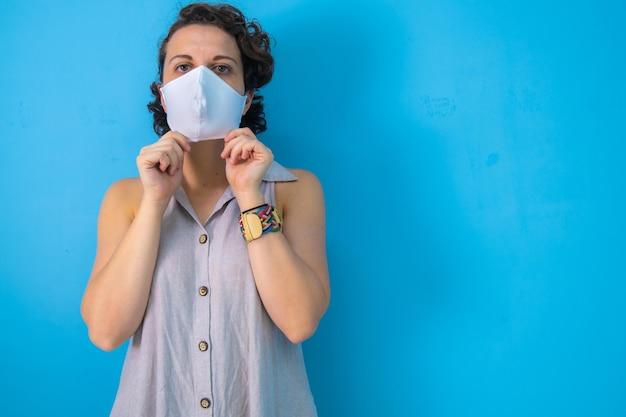 Vrouw op blauwe achtergrond die zich voorbereidt om haar masker af te doen na de pandemie met kopieerruimte