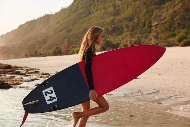 Vrouw op blote voeten staat zijwaarts, houdt een surfplank vast, geniet van vrije tijd om te surfen, poseert in de oceaan nabij de kust, tegen de rots