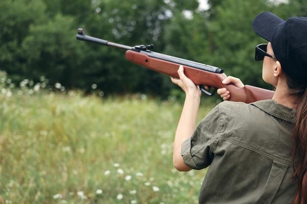 Vrouw op buiten met een pistool in de buurt van zijn hoofd zicht jacht op groene bladeren