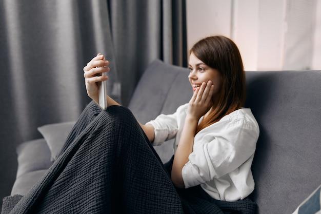 Vrouw op de bank met een deken op haar schoot en een mobiele telefoon in haar hand