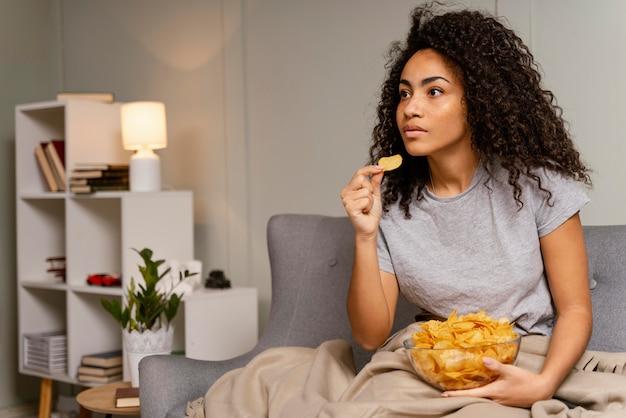 Vrouw op de bank tv kijken en chips eten