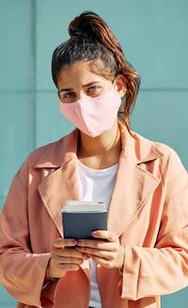 Vrouw op de luchthaven tijdens pandemie met medisch masker en paspoort