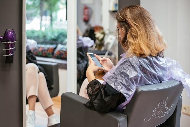 Vrouw op de mobiele telefoon die bij een haarsalon wacht