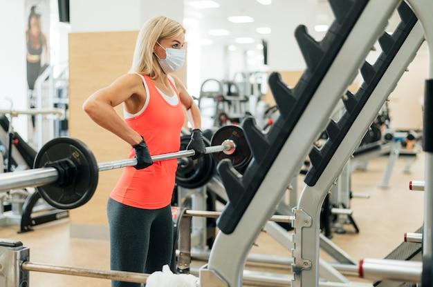 Vrouw op de sportschool doet training met medisch masker