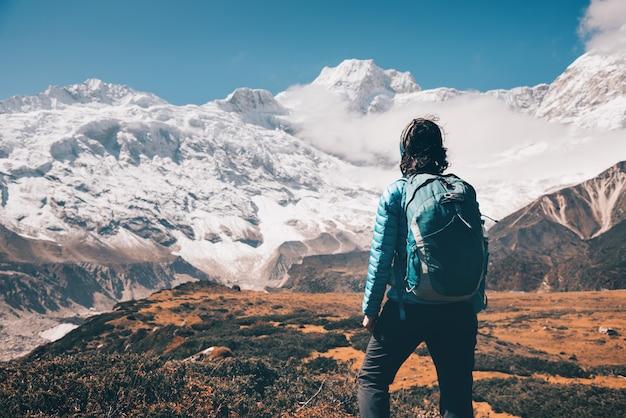 Vrouw op de steen en bergvallei