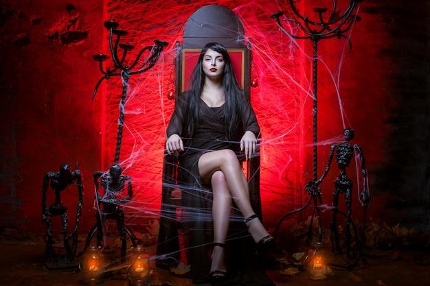 Vrouw op de troon in rode kamer in het donker