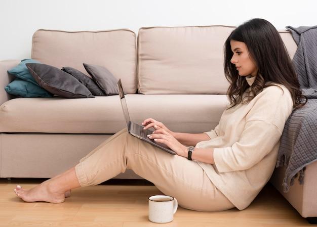 Vrouw op de vloer die op laptop werkt