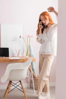 Vrouw op de werkplek met behulp van mobiel