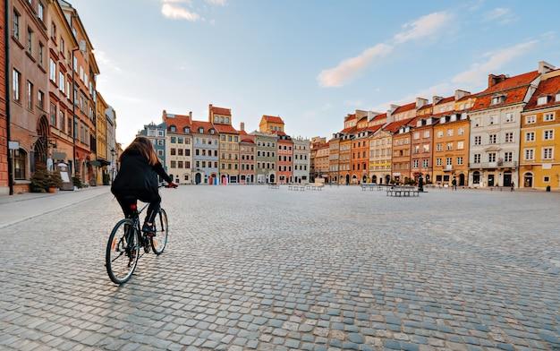 Vrouw op een fiets rijdt op een leeg oud stadsplein in warschau, polen