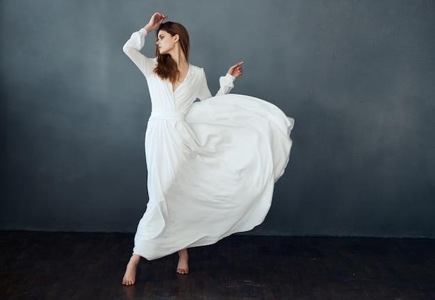 Vrouw op een grijze achtergrond in een witte jurk dansmodel in volle groei