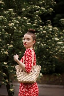 Vrouw op een groen park. rode zomerjurk, een stro gevlochten tas erbij. zomerse wandeling in het park
