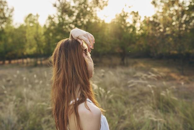 Vrouw op een weiland in de natuur en zomer bomen vakantie model zon.
