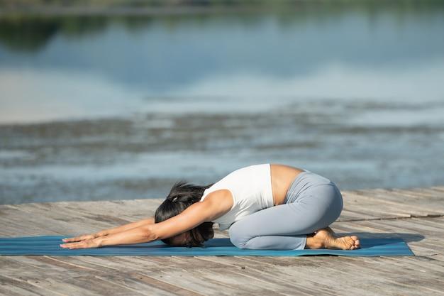 Vrouw op een yogamat om te ontspannen in het park bij bergmeer. aantrekkelijk sportief meisje in sportkleding. sportief meisje uit te werken. gezonde sportlevensstijl. atletische jonge vrouw in het doen van fitness oefening.