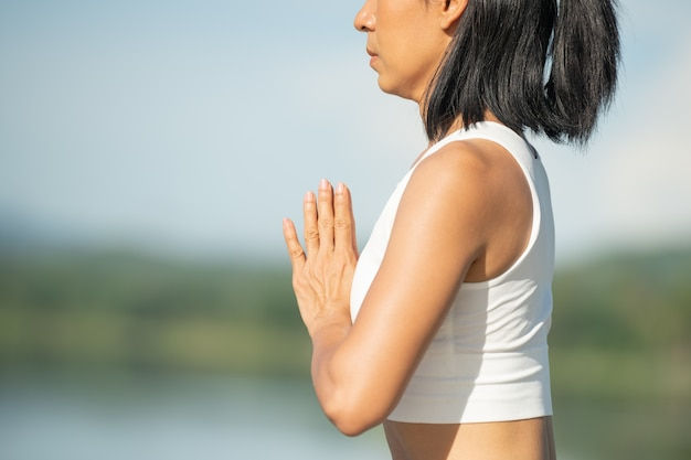 Vrouw op een yogamat om te ontspannen in het park bij bergmeer. kalme vrouw met gesloten ogen beoefenen van yoga, zittend in padmasana pose op de mat, lotus oefening, aantrekkelijk sportief meisje in sportkleding.
