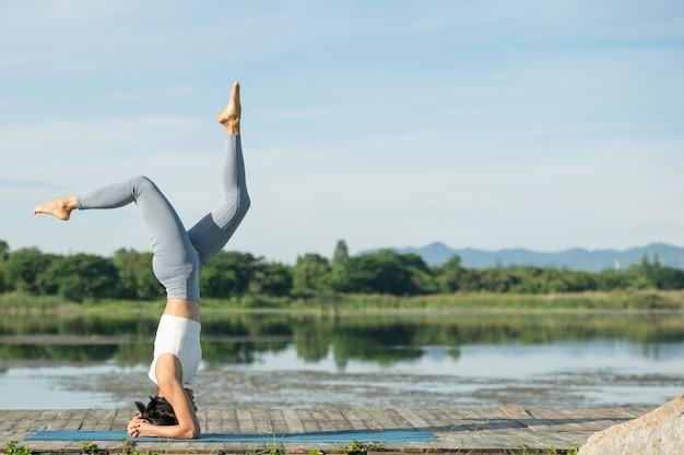 Vrouw op een yogamat om te ontspannen in het park. jonge sportieve aziatische vrouw die yoga beoefent, hoofdstandoefening doet, uitwerkt, sportkleding, broek en top draagt.