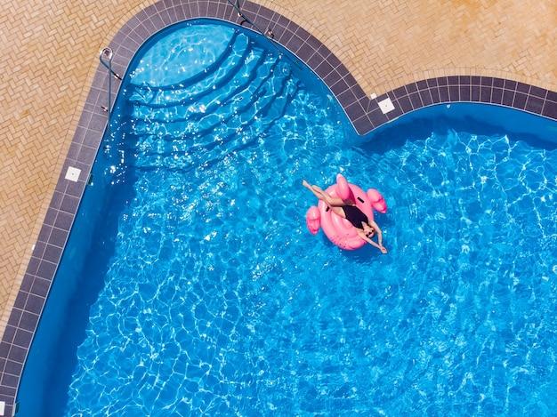 Vrouw op flamingo zwembad drijven in zwembad in het hotel, drone luchtfoto