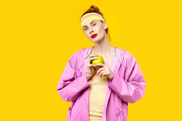 Vrouw op gele achtergrond en een roze jas houdt een appel