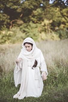 Vrouw op haar knieën terwijl ze een bijbels gewaad draagt