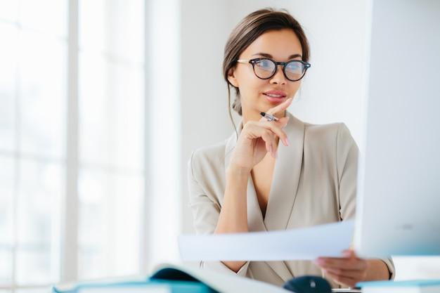 Vrouw op het kantoor dat door documenten wordt omringd