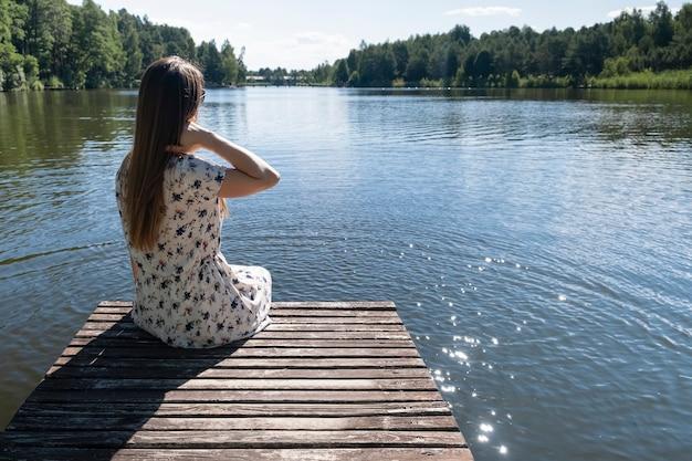 Vrouw op het meer. jonge vrouw, gekleed in witte jurk genieten van de natuur en rust zittend op een houten pier op het meer, achteraanzicht