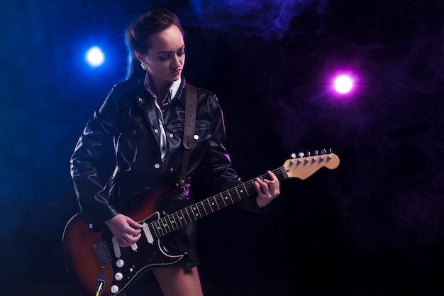 Vrouw op het podium met een gitaar en riem