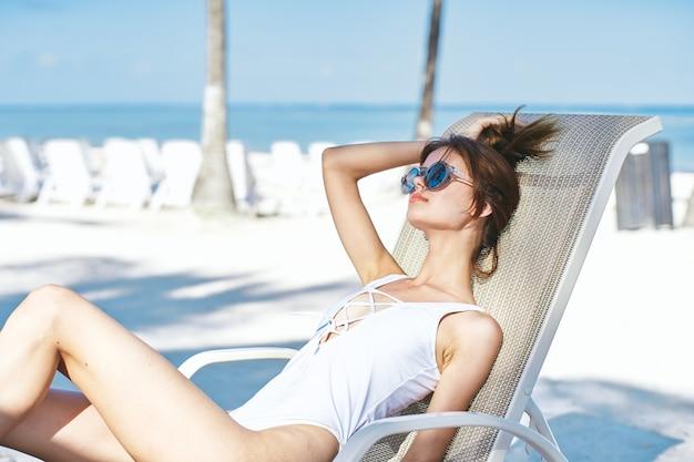 Vrouw op het strand aan zee op een zonnebank