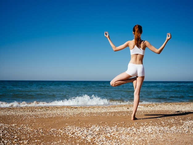 Vrouw op het strand die een wit zwempak draagt die yoga doet