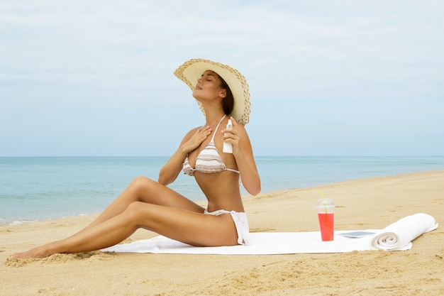 Vrouw op het strand die zonneschermnevel op haar lichaam toepassen