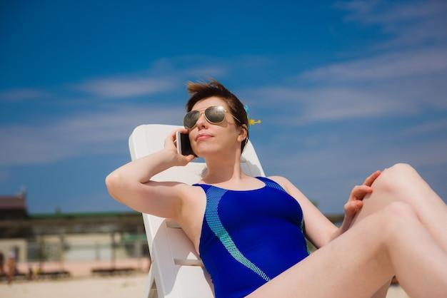 Vrouw op het strand in blauwe zwemkleding praten aan de telefoon