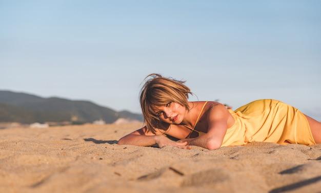 Vrouw op het strand in gele jurk. zonsondergang tijd vrouwelijk portret