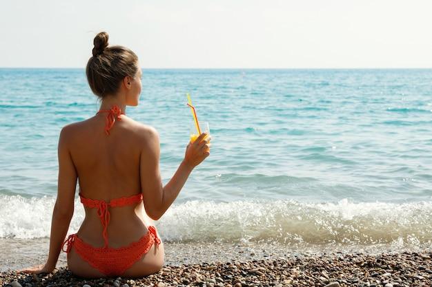 Vrouw op het strand met een glas cocktail