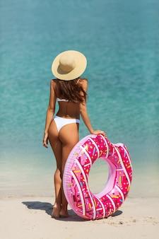 Vrouw op het strand met een rubberen ring.