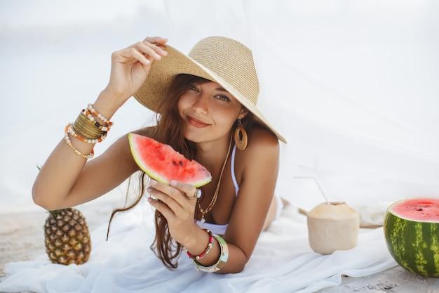 Vrouw op het tropische strand eten watermeloen