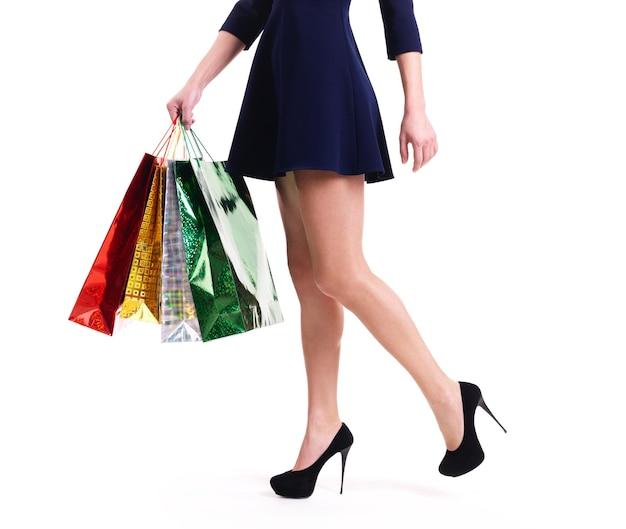 Vrouw op hoge hakken met kleur boodschappentassen staan - geïsoleerd op wit.