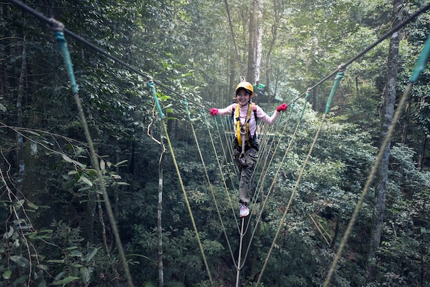 Vrouw op kabels in een avonturenpark op een moeilijke weg