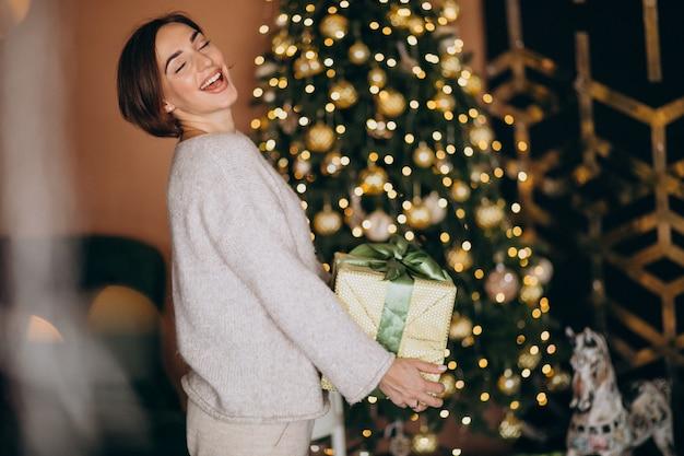 Vrouw op kerstmis die kerstmis huidig houdt door de kerstmisboom