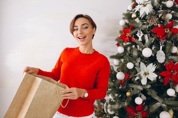 Vrouw op kerstmis met giften door kerstmisboom
