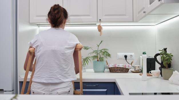 Vrouw op krukken doet de afwas in de keuken