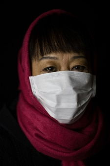 Vrouw op middelbare leeftijd met een kastanjebruine hijab die een gezichtsmasker draagt
