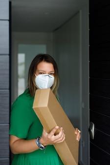 Vrouw op middelbare leeftijd met een masker dat een pakket thuis opneemt