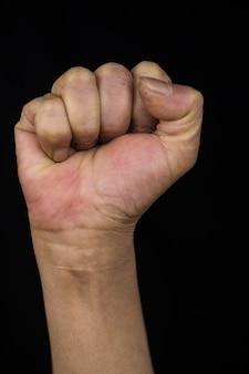 Vrouw op middelbare leeftijd met gestrekte arm die haar vuist toont die vrouwenemancipatie en rechten toont