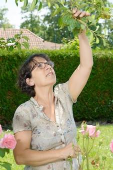 Vrouw op middelbare leeftijd met glazen in de tuin