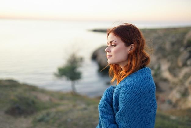 Vrouw op natuur blauwe plaid bewondert de landschapsreizen