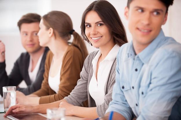 Vrouw op seminar. groep jonge mensen die samen aan tafel zitten terwijl een mooie vrouw naar de camera kijkt en glimlacht