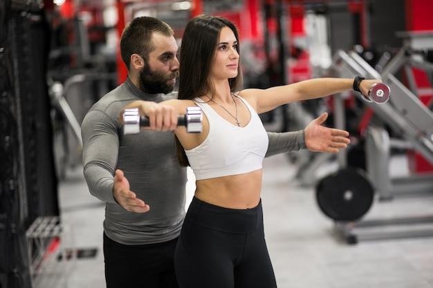 Vrouw op sportschool met trainer