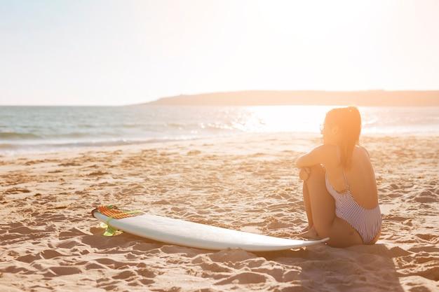 Vrouw op strand met surfplank