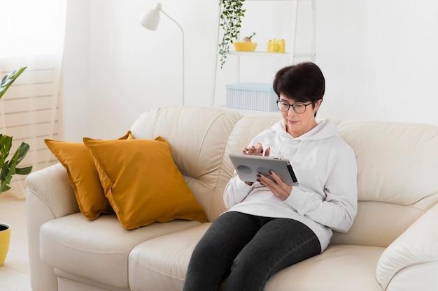 Vrouw op tablet thuis