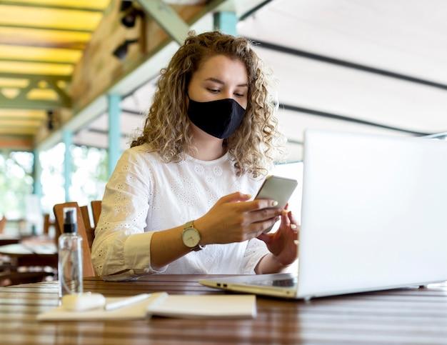 Vrouw op terras met masker met behulp van telefoon