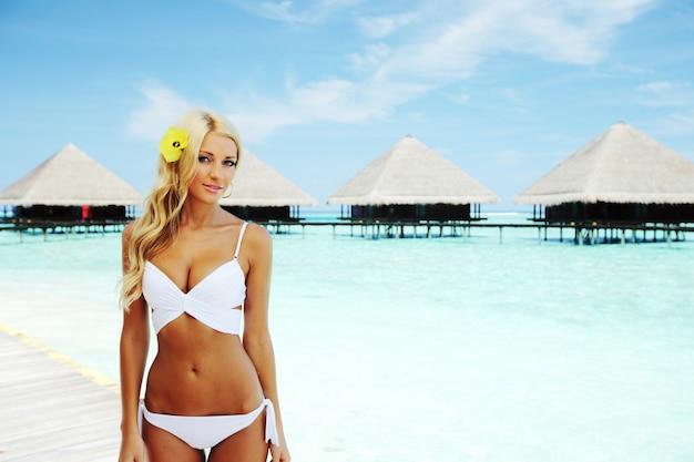 Vrouw op tropisch strandhuis terug